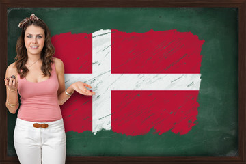 Beautiful and smiling woman showing flag of Denmark on blackboar