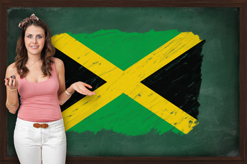 Beautiful and smiling woman showing flag of Jamaica on blackboar