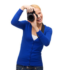 smiling woman taking picture with digital camera