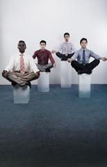 Four businessmen practicing yoga