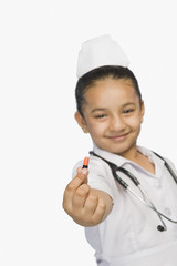 Girl dressed as a nurse and holding a capsule and smiling