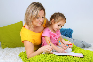 Wall Mural - Little girl with mom read book in bed