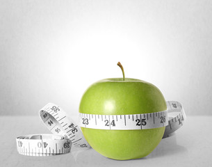 Green apple with measurement on a gray background