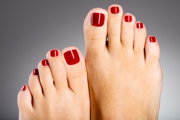 Wall Murals Pedicure Beautiful female feet with red pedicure