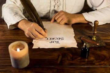 Mann schreibt Top Secret auf Pergament