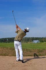 Golf, golfer striking the ball from the bunker