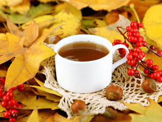 Cup of hot beverage, on yellow leaves background