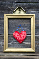 vintage golden picture frame with red heart on wall