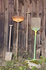 farmer gardener tools near  wooden barn wall