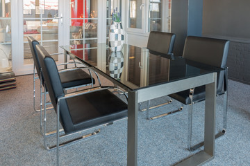 Showroom of furniture store with modern glass table and chairs