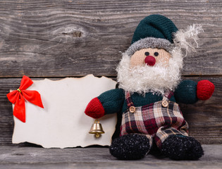 Santa Claus toy against wooden background with blank paper- Mess