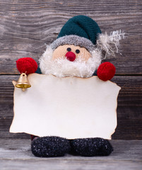 Santa Claus toy holding empty paper against wooden background