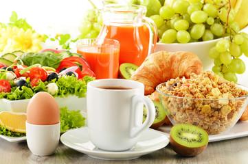 Breakfast with coffee, juice, croissant, salad, muesli and egg