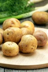 Raw potatoes on the cutting board