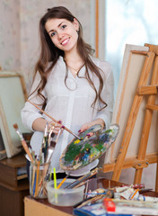 Happy girl paints on canvas with oil colors