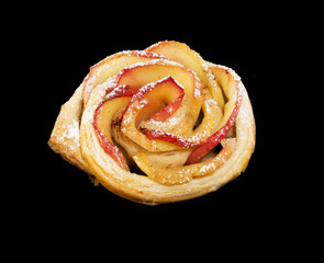 Sweet roll with apples in the form of roses on black  background