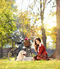 Pretty female sitting down with her dog in a park
