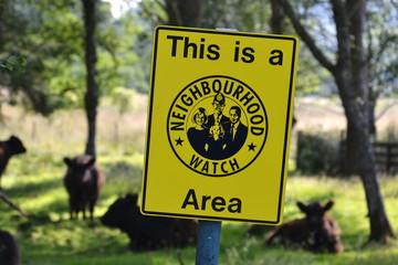 Neighborhood watch sign in cow paddock, Scotland