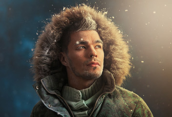 Portrait of brutal sexy man outdoors in winter under snowstorm