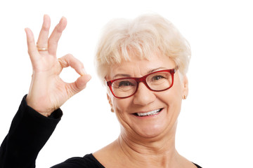 Happy old woman in eye glasses showing OK.