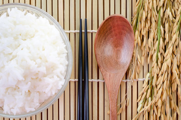 bowl of white steamed rice with chopsticks on bamboo mat.with pa