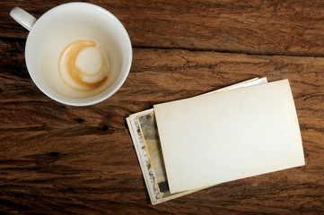 Empty coffee cup and old paper photo frame on wood background