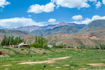 Wall Mural - Village and colorful mountains of Tien Shan