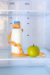 Conceptual photo of diet: apple and milk bottle with measuring