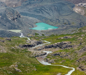 Fototapete - Heart-shaped lake and river flowing from glacier