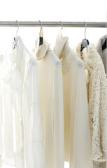 Fashion female white clothing hanging on hangers