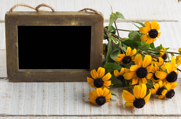 Autumn flowers on table with empty blackboard