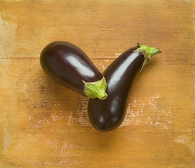 Two eggplants on a wooden board