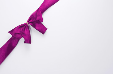 purple ribbon with bow with tails isolated on white background
