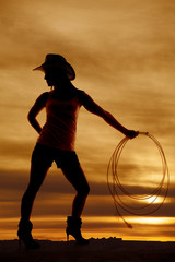 silhouette woman cowgirl hat look back rope