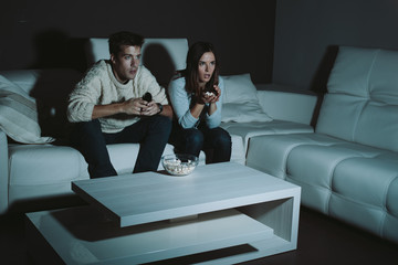 Young couple watching TV late at night