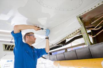 Engineer assembling wing of passenger jet in hangar