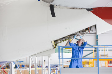 Engineer repairing passenger jet in hangar