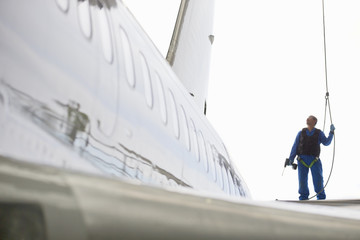 Engineer in harness next to passenger jet in hangar