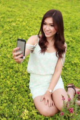 young woman taking a self portrait by using mobile phone