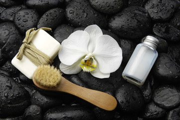 Set of with white orchid ,soap , brush, on wet pebbles