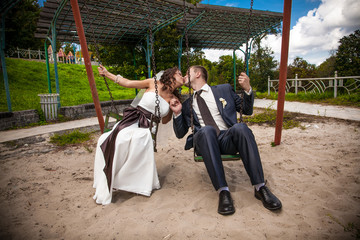 Young groom and bride kissing on swing at playground