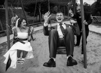 photo of newly married couple swinging on playground