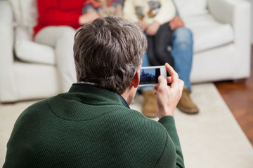 Father Photographing Family Through Smartphone
