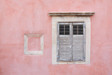 Exterior pink wall with shuttered wooden window