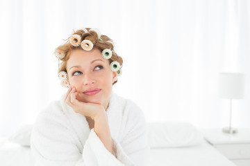 Thoughtful woman in bathrobe and hair curlers sitting on bed