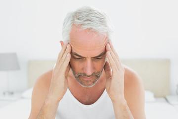 Man suffering from headache in bed