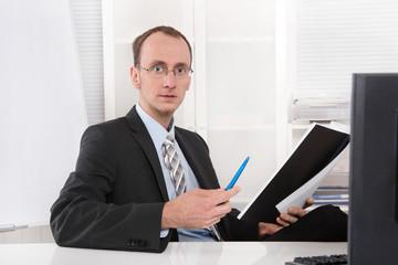 Freundlicher Chef oder Manager sitzend am Schreibtisch