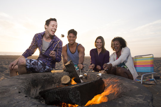 Two young couples making S'mores on the beach