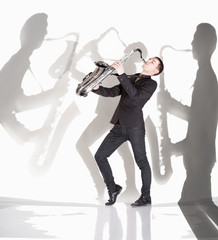 saxophonist  playing against background with shadow of musicians