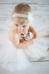 Cute baby ballerina on a floor